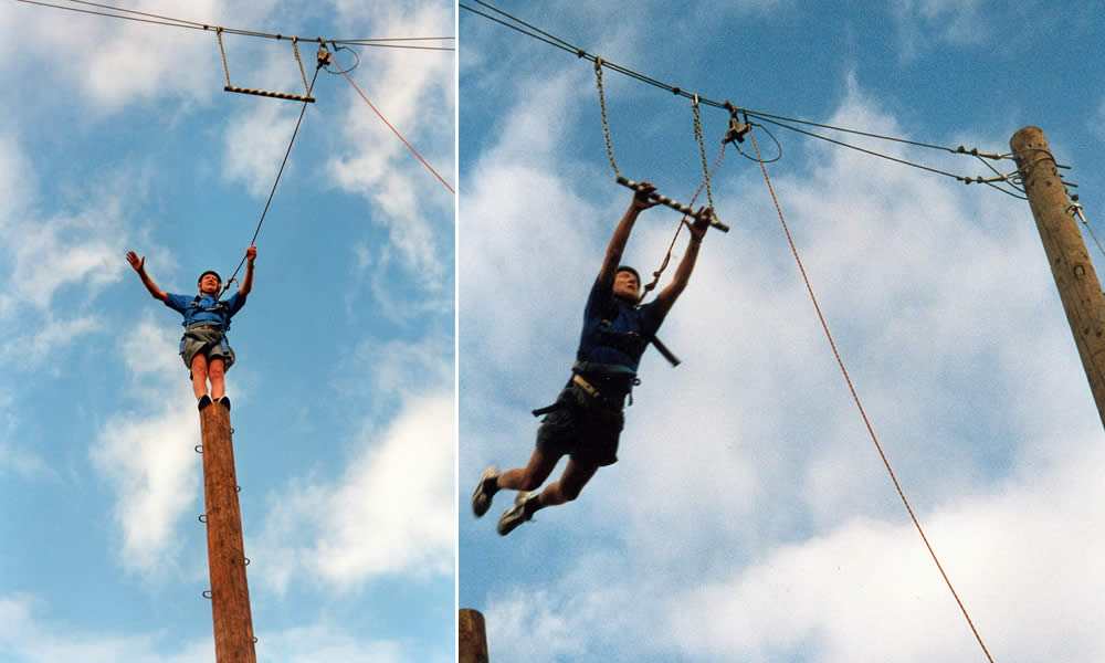 Waldemar standing atop the 50 ft . pole and jumping out onto the mid air trapeze.